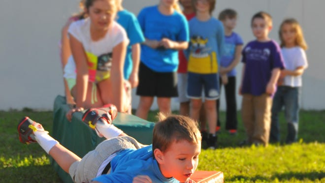 """Ben Branan, 9, makes his way across the course with out touching the grass. With the popularity of """"Ninja Warrior"""" and similar shows, family activities are taking on a gladiator-type feel. Reed Tompkins teaches """"Lil Sports"""" to young children at the DRS Community Center in Satellite Beach."""