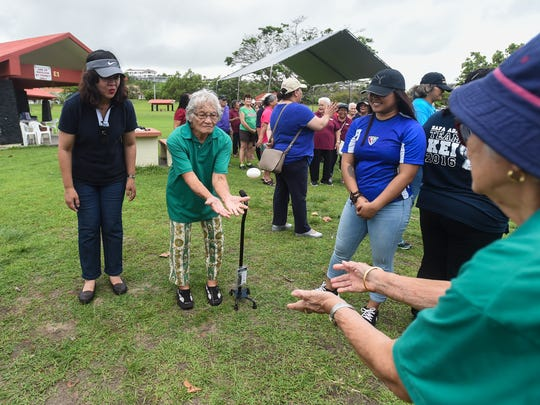 Yigo resident Auginnia Tornilla, 88, concentrates on a catch during an egg toss game at the third annual Huegon-Manamko' Senior Games in Tumon on April 27, 2018.