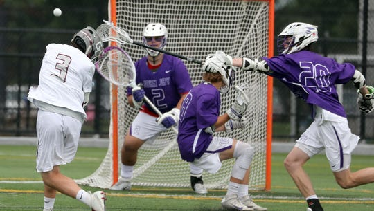 Garden City's Liam Muldoon shoots on John Jay goalie