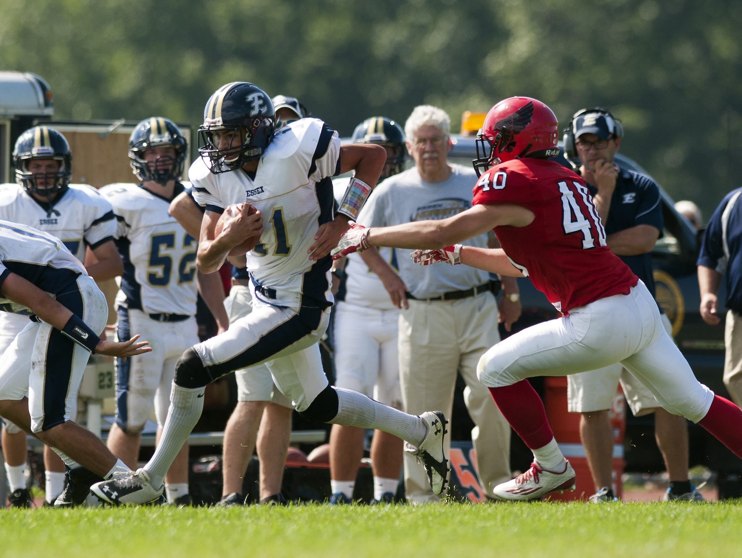 Essex quarterback Eli DiGRande (11) runs past CVU's Tristan Nagiba (40) with the ball during the high school football game between the Essex Hornets and the Champlain Valley Union Redhawks on Saturday afternoon.