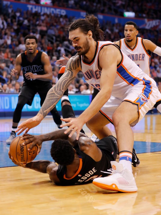 Oklahoma City Thunder center Steven Adams, top, and Phoenix Suns guard Eric Bledsoe reach for a loose ball during the second half of an NBA basketball game in Oklahoma City, Friday, Oct. 28, 2016. Oklahoma City won 113-110. (AP Photo/Alonzo Adams)