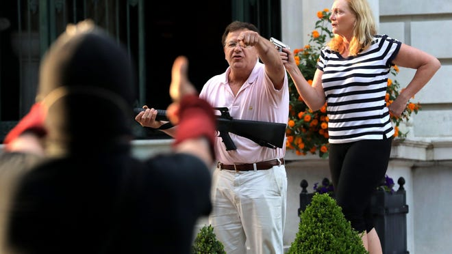 FILE - In this June 28, 2020 file photo, armed homeowners Mark and Patricia McCloskey, standing in front their house along Portland Place confront protesters marching to St. Louis Mayor Lyda Krewson's house in the Central West End of St. Louis. St. Louis' top prosecutor told The Associated Press on Monday, July 20, 2020 that she is charging a white husband and wife with felony unlawful use of a weapon for displaying guns during a racial injustice protest outside their mansion.