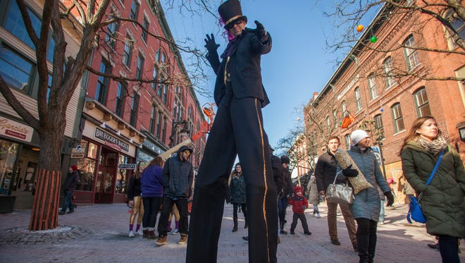 Tall man, Michael Schruefer, from New Jersey, struts down Church Street for Magic Hat's Mardi Gras parade 2015.