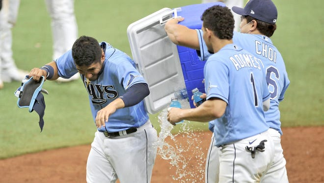 Tampa Bay Rays Michael Perez, Willy Adames and Ji-Man Choi (from left) celebrate a win over the New York Yankees Sunday in St. Petersburg, Florida.