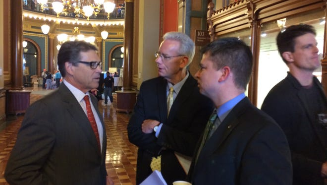 Former Texas Gov. Rick Perry, left, chatted up Iowa state Reps. Ron Jorgensen, center, and Quentin Stanerson, right, during a visit to the Iowa Capitol on Monday, Jan. 26, 2015.