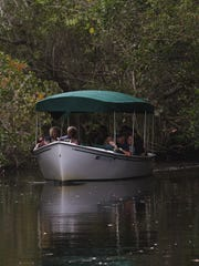 Visitors take a ride on the electric boat at the Conservancy