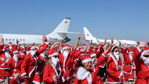 A group of people dressed as Santa dash across the