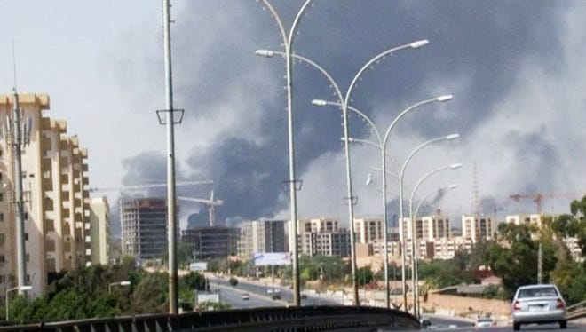 This  file image made from video by The Associated Press on July 13, 2014, smoke rises from the direction of Tripoli airport in Tripoli, Libya. T