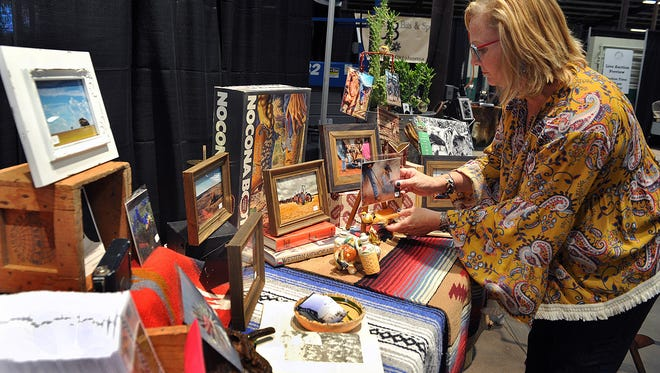 In this 2017 file photo, Willetta Crowe, a photographic artist from Nocona, sets up her exhibit at the Bridwell Ag Center for the annual Cowboy True Western art event. This year's event will be held March 20 and 30 at The Forum, and is free to the public.
