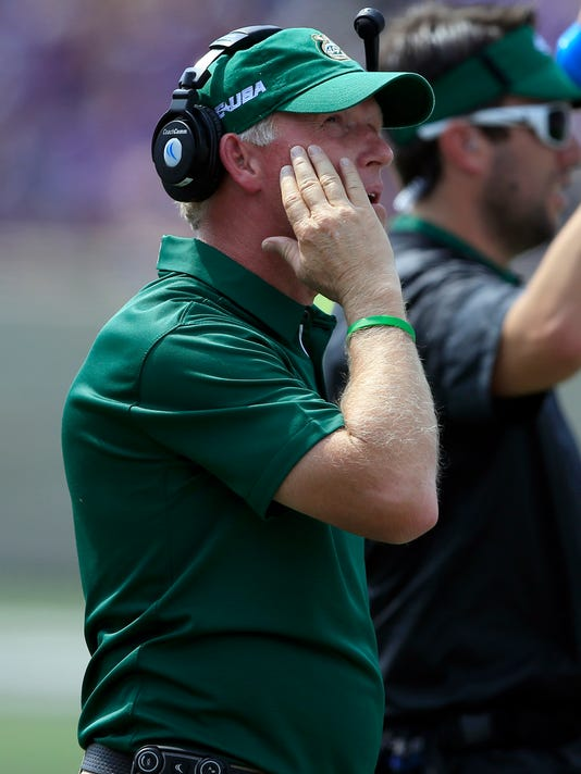 Charlotte head coach Brad Lambert looks at the scoreboard during the first half of an NCAA college football game against Kansas State in Manhattan, Kan., Saturday, Sept. 9, 2017. (AP Photo/Orlin Wagner)