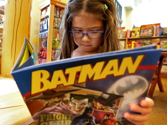 Lucy Gannon, 7, of West Des Moines, looks at a Batman
