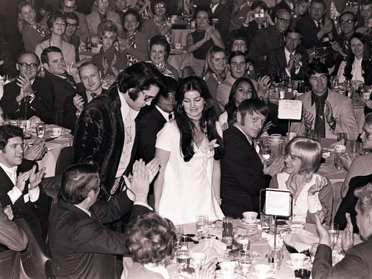 Elvis Presley and wife, Priscilla, stand as he is introduced