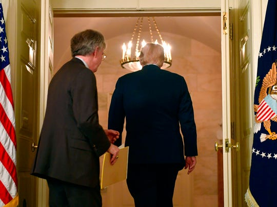 National security adviser John Bolton, left, follows President Donald Trump from the room after he spoke in the Diplomatic Reception Room of the White House on Friday, April 13, 2018, in Washington, about the United States' military response to Syria's chemical weapon attack on April 7. (AP Photo/Susan Walsh)