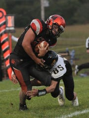 Lucas quarterback Jeb Grover is tackled by Northmor's Noah Trainer in Friday night's game.