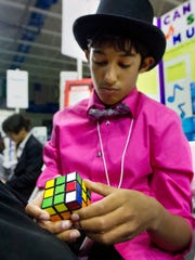 Joel Arias, 12, solves a Rubik's Cube while waiting for judging Saturday at the Thomas Alva Edison Kiwanis Science and Engineering Fair at Alico Arena in Fort Myers. Students fill the down time at the fair by reading as well.