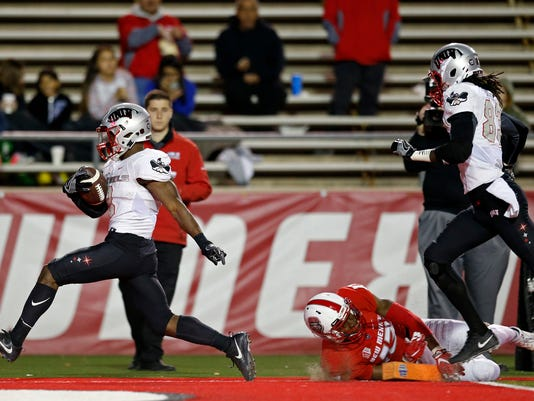UNLV running back Lexington Thomas, left, scores a touchdown past New Mexico cornerback Jalin Burrell (13) during the first half of an NCAA college football game in Albuquerque, N.M., Friday, Nov. 17, 2017. (AP Photo/Andres Leighton)