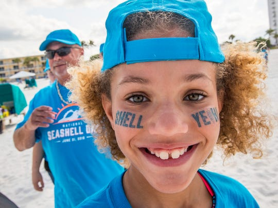 Alexi Borne, 11, from Louisiana, went to the beach to participate. At The Outrigger Beach Resort tiki hut on Fort Myers Beach, just over 1,000 volunteers gathered on National Seashell Day to form a human seashell.