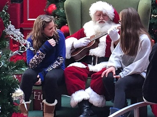 Fourteen-year-olds Allyson Wallauer and Camrin Laterza, both of Pennsylvania, get serenaded by Santa at Christiana Mall Friday.