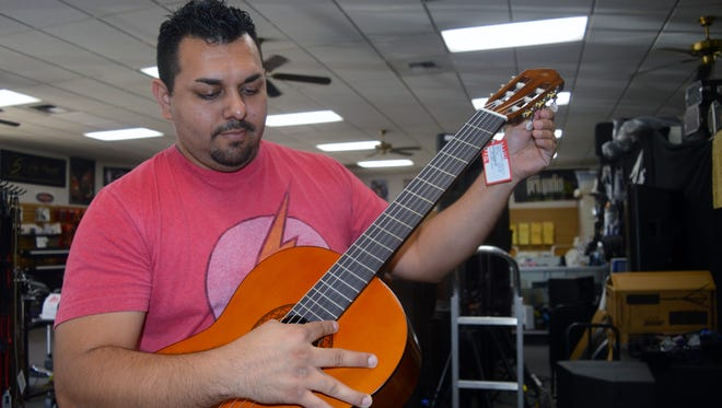 Joseph Vasquez, Whites Music Center employee, showcases the difference between the types of guitars sold at the store.