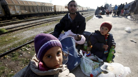 A man with children, refugees from Syria, rest at the