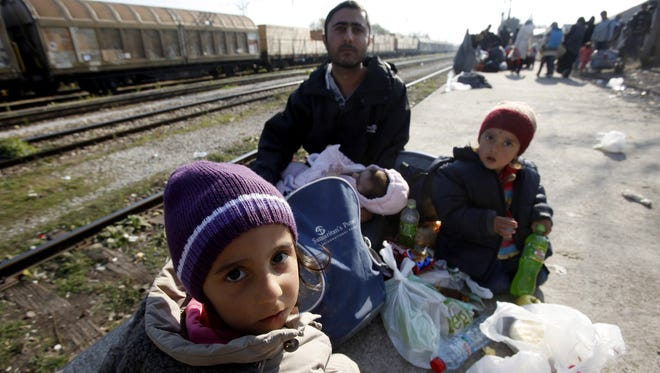 A man with children, refugees from Syria, rest at the transit center for refugees near the village of Tabanovce, in northern Macedonia, before continuing their trip to the border with Serbia, Friday, Nov. 20, 2015. Macedonia, along with Serbia, Croatia and Slovenia, has begun turning away migrants who are not from war zones such as Syria, Afghanistan and Iraq.