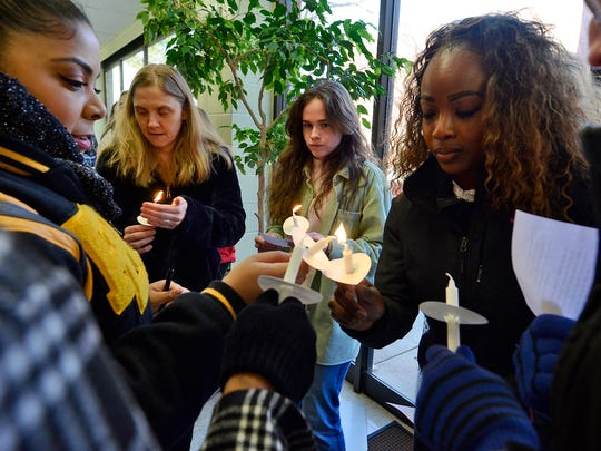 Penn State York student Shayla Jones, left, 19 of Red Lion, lights candles for fellow students during the seventh annual candlelight vigil for child abuse awareness, Thursday, April 5, 2018.  John A. Pavoncello photo