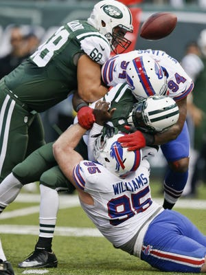 New York Jets quarterback Michael Vick is sacked by Buffalo Bills' Mario Williams (94) and Kyle Williams (95) during an Oct. 26 game in East Rutherford, N.J.