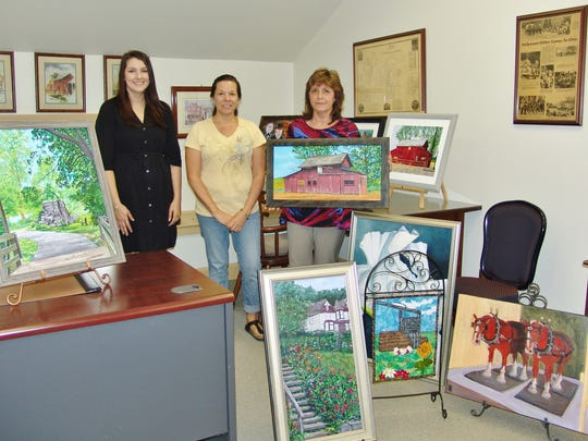 Mariah Ellenwood, Shara Prindle and Lynda Daniel pose with artwork that has been submitted in the Canal Era Art Contest for judging on Member Day.