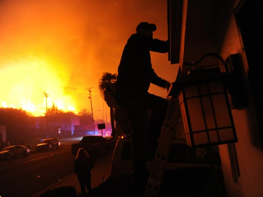 The Hawaiian Village Apartments burn in the Thomas Fire as a neighborhood resident climbs to his rooftop with a hose on Poli Street in Ventura.