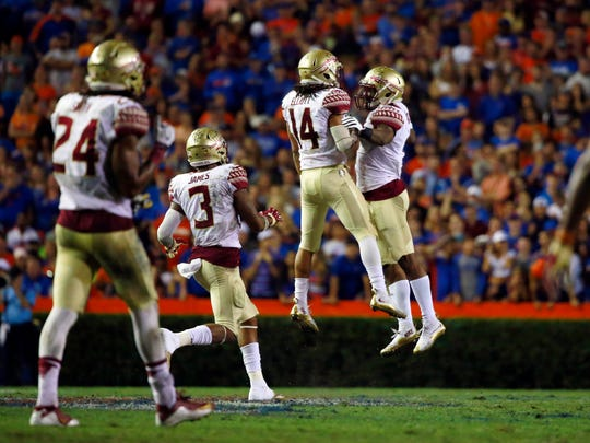Nov 28, 2015; Gainesville, FL, USA; Florida State Seminoles defensive back Javien Elliott (14) is congratulated by defensive back Tyler Hunter (1) after sacking Florida Gators quarterback Treon Harris (not pictured) during the second half at Ben Hill Griffin Stadium. Florida State defeated Florida 27-2.  Mandatory Credit: Kim Klement-USA TODAY Sports