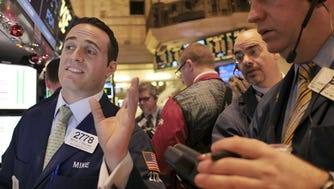 Traders work on the floor at the New York Stock Exchange on Thursday, Dec. 18, 2014.  (AP Photo/Seth Wenig)