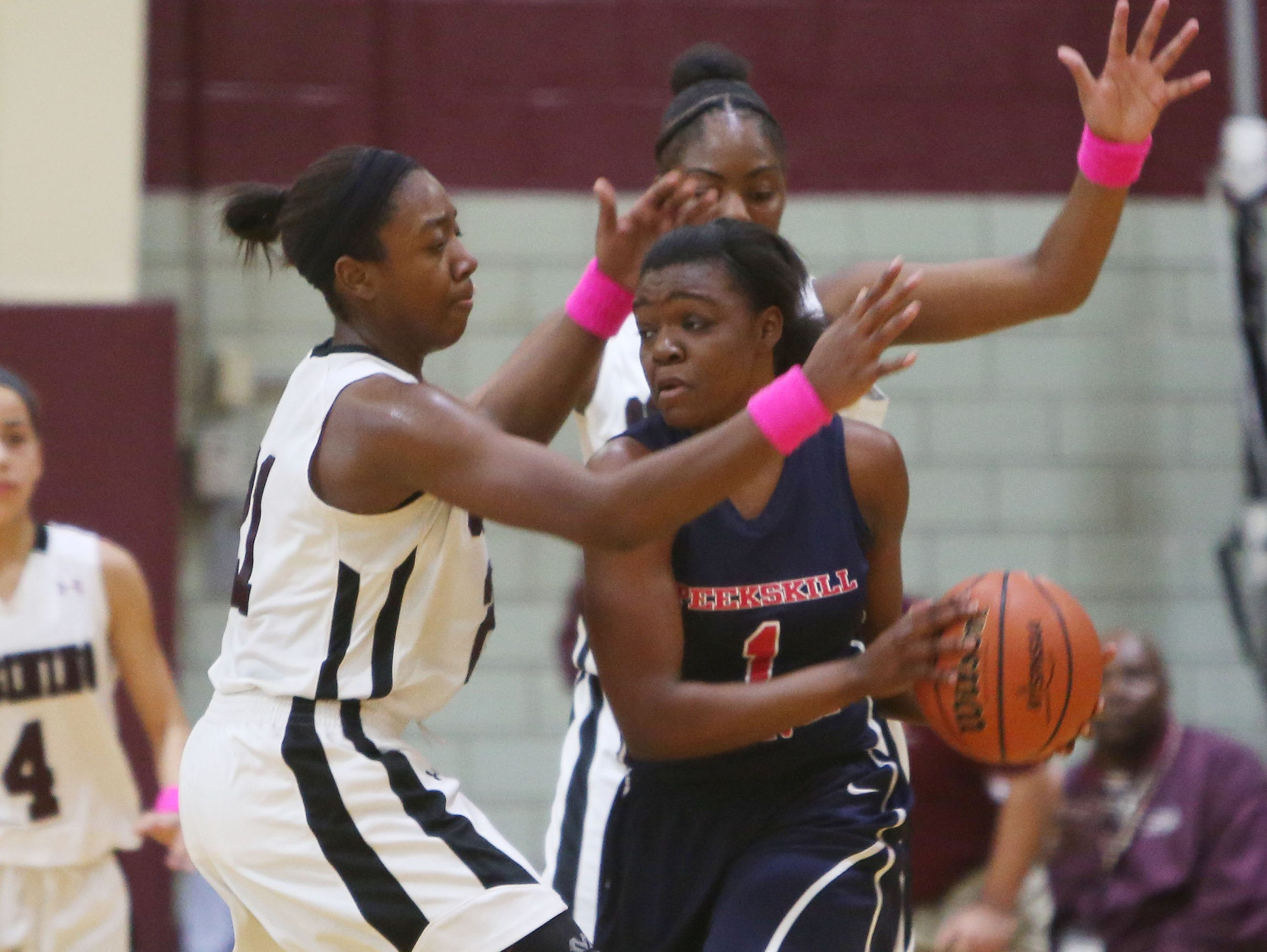 Peekskill's Lanay Rodney looks for a teammate while getting pressure from Ossining's Shadeen Samuels during their game Tuesday at Ossining High School.