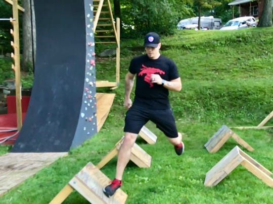 Eric Totten practices on the ninja obstacle course he created in his Rockaway Township backyard.