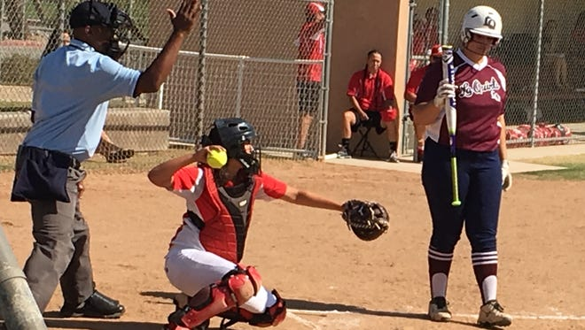 The umpire calls a strike as Palm Springs catcher Alyssa Ayala holds the ball while La Quinta's Lauren Robinson looks on Tuesday. The Blackhawks won 11-4.