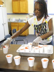 Janessa Hairston lines cups of watermelon in preparation
