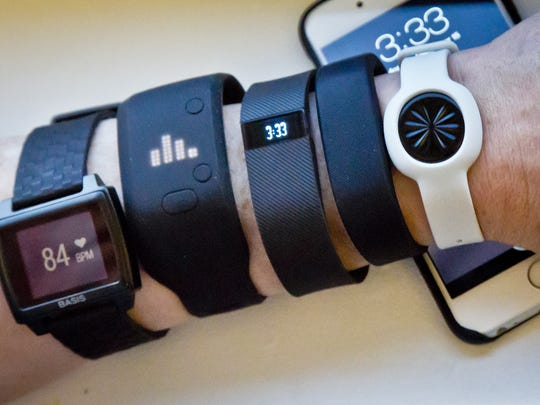 Fitness trackers, from left, Basis Peak, Adidas Fit Smart, Fitbit Charge, Sony SmartBand and Jawbone Move, next to an iPhone.