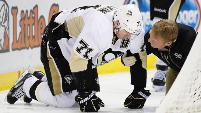 Pittsburgh Penguins center Evgeni Malkin get checked by the trainer after getting injured in the third period against the Detroit Red Wings on Saturday.
