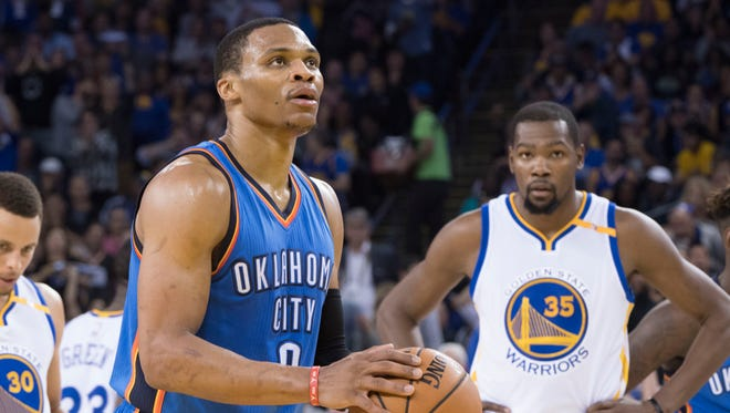 Oklahoma City Thunder guard Russell Westbrook (0) shoots a technical foul shot as Golden State Warriors forward Kevin Durant (35) looks on during the second quarter at Oracle Arena.