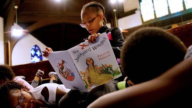 Avion Evans reads a book next  Zariah Sheppard during morning reading time at the Freedom School at Mother African Union Church.