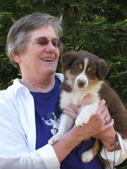 FILE - In this 2012 file photo provided by George Powell, his wife Lynne Powell picks up her border collie Jemma from the breeder in Grants Pass, Ore. Lynne's car that had gone off the road and into a ravine in the heavy smoke from a wildfire in California. After searching for her all night and the next day, a detective called to tell George that Lynne's body was found near her car. (George Powell via AP, File)