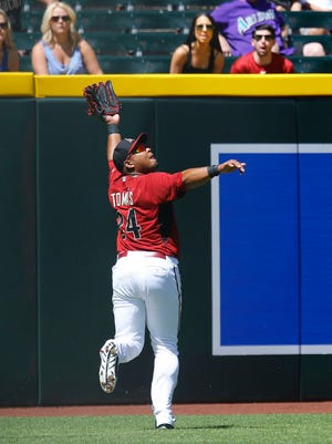Arizona Diamondbacks left fielder Yasmany Tomas (24) makes a over the shoulder catch on a hit by Chicago Cubs' Albert Almora (78) in the second inning of their spring training game Saturday, April 4, 2015 in Phoenix, Ariz.