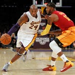 FILE - In this Jan. 15, 2015, file photo, Los Angeles Lakers guard Kobe Bryant, right, and Cleveland Cavaliers forward LeBron James hug before the start of an NBA basketball game, in Los Angeles.