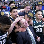 The Michigan State Spartans celebrate with head coach Tom Izzo after a game against the Louisville Cardinals.