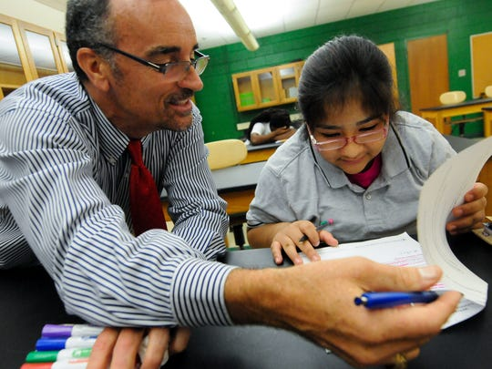 Thomas Gaynor helps Zenen Salazar-Lopez, 13, of Wilmington, with an information packet in her seventh grade science class that currently has no permanent teacher at Bayard Middle School in Wilmington on Sept. 14. Some schools are dealing with high turnover among educators.