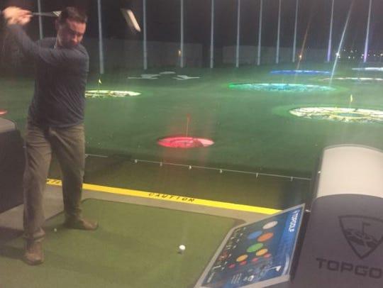 Matt Tapia takes a practice swing at the Topgolf Nashville