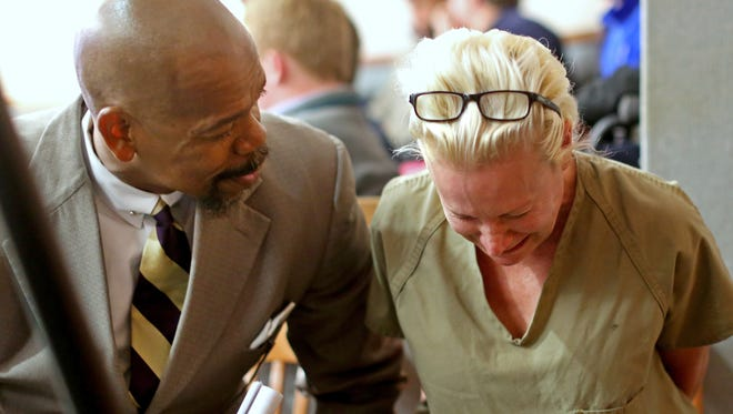 Crysta Pleatman breaks down prior to going before Judge Fanon Rucker in his Hamilton County court room for a bond hearing on two of her four criminal cases. At left is her attorney, Clyde Bennett II. Her bond was set at $35,000 and she was ordered to stay in jail until her trial begins next week. Pleatman is the defendant in the Indian Hill real estate case.