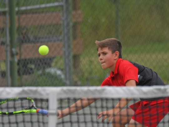 Harrison Arnholt reaches for a volley in the boys 12