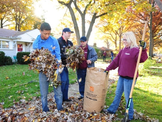 Redford Explorer Clifford Stafford, Redford Firefighter Joseph Kleehamer and Redford Jaycee members Brandon Gilbert and Stephanie Johnson help clean up a seniors yard on  Brady St. during the eighth annual Make a Senior Smile Day event sponsored by Wayne County Commissioner Diane Webb.