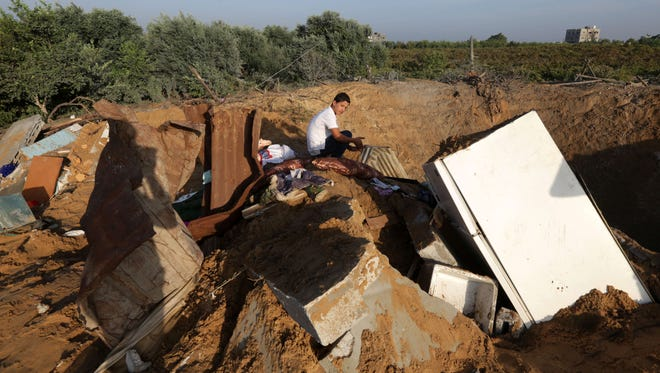 A Palestinian boy inspects the damage after an Israeli retaliatory air strike demolished the house of a Palestinian family on October 11, 2015 in the Zeitun sector south of Gaza City. A pregnant Palestinian mother and her toddler daughter were killed in the air strike.