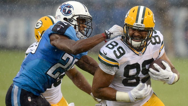 Tennessee Titans cornerback Blidi Wreh-Wilson (25) tries to bring down Green Bay Packers tight end Richard Rodgers (89) in the first quarter of a preseason NFL football game Saturday, Aug. 9, 2014, in Nashville, Tenn. (AP Photo/Mark Zaleski)